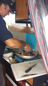 Captain Tore cooking up the best seasfood risotto on his boat in Sardinia